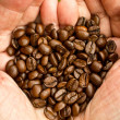 Handful of coffee beans in hands — Stock Photo
