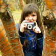 Girl with camera behind a tree — Stock Photo