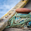 Stock Photo: Maritime bollard loosely wound with colorful mooring warps