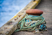 Maritime bollard loosely wound with colorful mooring warps — Stock Photo