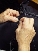 Tailor hands sewing a coat — Stock Photo
