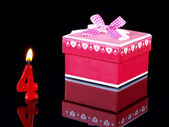 Birthday-anniversary gift with red candles showing Nr. 4 — Stock Photo