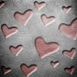 Grunge wall with hollowed red hearts — Stock Photo