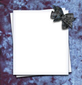 Paper blank with bow in corner on velvet fabric — Stock Photo