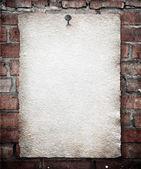 Altpapier auf ziegelmauer — Stockfoto