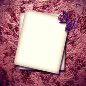 Paper blank with bow in corner on stone background — Stock Photo