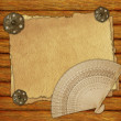 Vintage paper on wooden desk with brooch and fan — Stock Photo #34081465