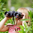 Child looking through binoculars — Stock Photo