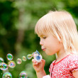 Little girl making bubbles — Stock Photo