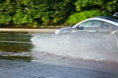 Car moving through puddle — Foto de Stock