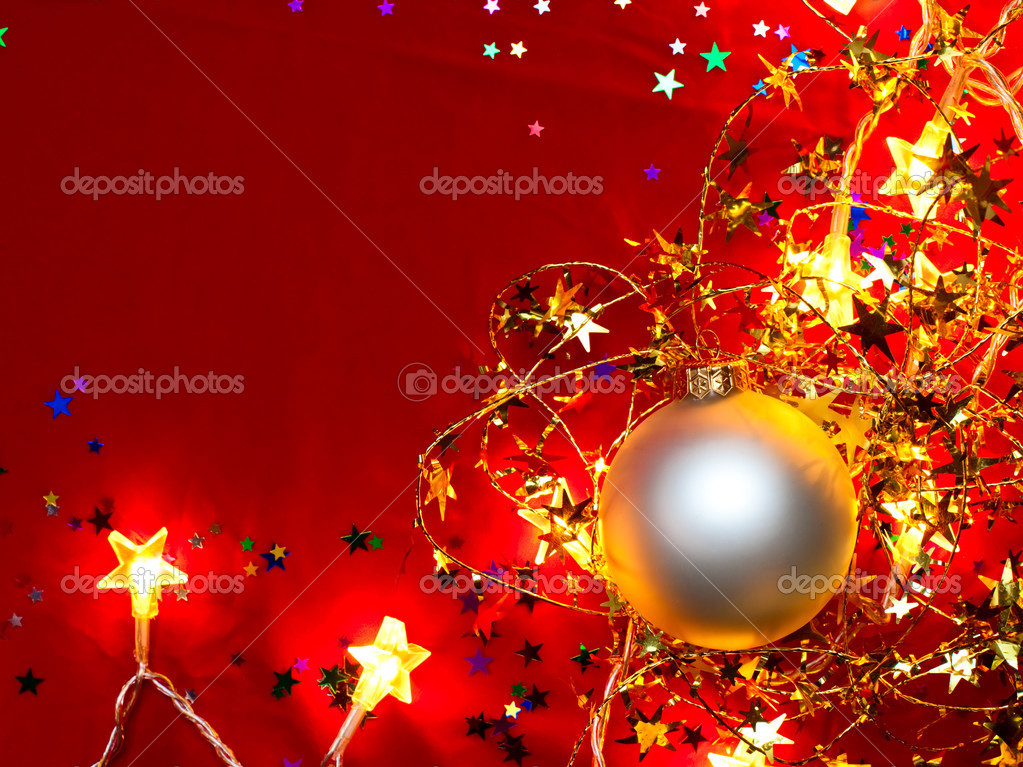 Christmas bauble with star-shaped lights and tinsel on red background — Stock Photo #13740617