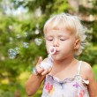 Little girl making bubbles — Stock Photo #14627435