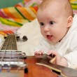 Infant and the bass guitar — Stock Photo