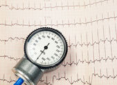 Blood pressure manometer on EKG — Stock Photo