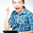 Royalty-Free Stock Photo: Boy cheering holding tablet computer