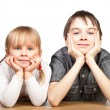 Sister and brother sitting at desk — Stock Photo