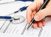 Hand with pen over Rx patient info — Stock Photo