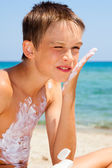Boy applying sunscreen — Stock Photo