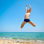 Boy jumping on the beach — Stok fotoğraf