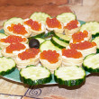 Appetizers with red caviar and a cucumbe — Stock Photo