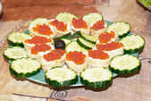 Appetizers with red caviar and a cucumbe — Zdjęcie stockowe
