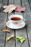 A white vintage cup of tea on grey rustic wooden table, with autumn leaves. — Stock Photo