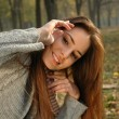 Smiling womremoving hair from her face in autumn park — стоковое фото #33664443