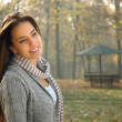 Pensive young woman smiling and posing in autumn park — Stock Photo