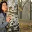 Pensive woman leaned on birch in autumn park — Stock Photo