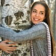 Woman smiling and hugging a birch tree — Stock Photo #33665717