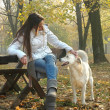 Young woman sitting on bench in autumn park cuddling dog) — Stock Photo