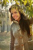 Woman peeking behind tree — Stock Photo