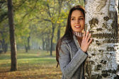 Beautiful woman smiling, leaned on a birch tree — Stock Photo