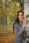Woman smiling, leaned on a birch tree — Stock Photo
