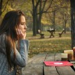 Woman at table in autumn park with paper and candles  — Stock Photo