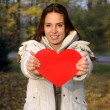 Beautiful woman in white jacket holding paper heart — ストック写真