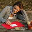 Woman writing word LOVE, paper on wooden table — Stock Photo