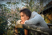 Beautiful woman leaning chin on old wooden fence, thinking — Stock Photo