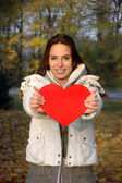 Beautiful woman in white jacket holding paper heart — Stock Photo