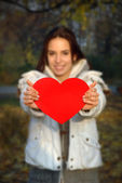 Woman out of focus holding paper heart — Stock Photo