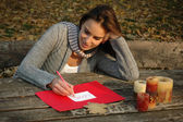 Woman writing word LOVE, paper on wooden table — Stockfoto
