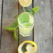 Top view of lemonade with mint, cut lemon and peel — Stock Photo #34483835