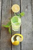 Top view of lemonade with mint, cut lemon and peel — Stock Photo