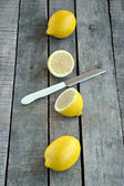Whole and cut lemon with knife on wood background — Foto de Stock