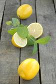 Celá a řez citronu s mátou na šedém pozadí dřevěná — Stock fotografie