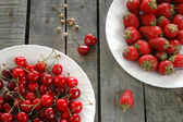Cherries and strawberries in plates on wooden background — Stock Photo