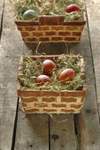 Cestini con uova di pasqua sul vecchio tavolo di legno — Foto Stock