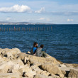 Young sitting on stony pier — Stock Photo