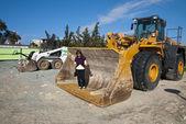 Woman in massive excavator bucket — Stock Photo