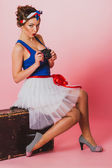 Pin up Girl With a Film camera seat on a luggage — Stock Photo